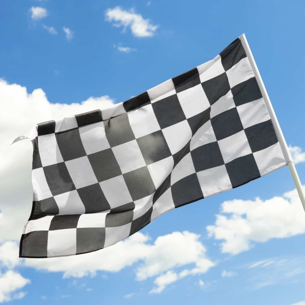 Checkered flag waving in the wind with white clouds on background - 1 to 1 ratio