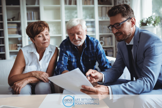 image of senior couple sitting in their home looking over papers with a financial advisor