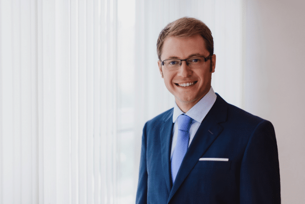 portrait of a smiling, blond financial advisor with glasses