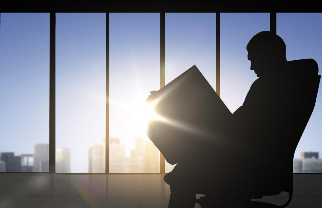 silhouette of financial planner studying life settlement documents