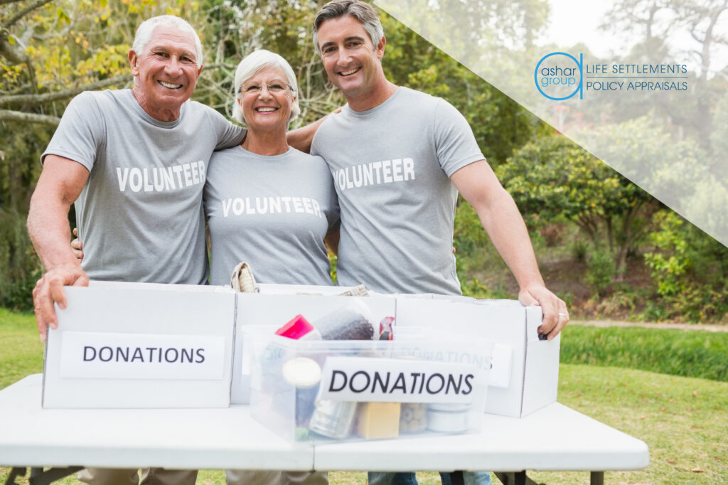 "3 retired seniors wearing shirts that say ""volunteer"" collecting donations in boxes"