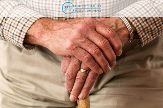 senior man in long-term care with folded hands on top of walking stick