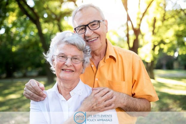 happy senior man and woman couple holding hands