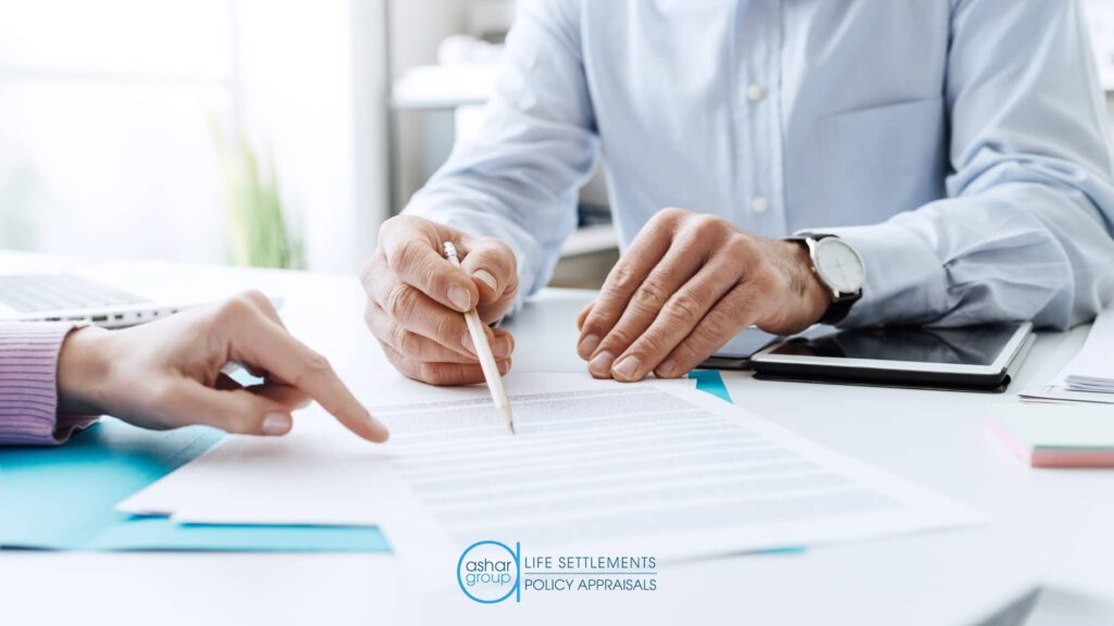 insurance advisor working on life settlement with client signing paperwork
