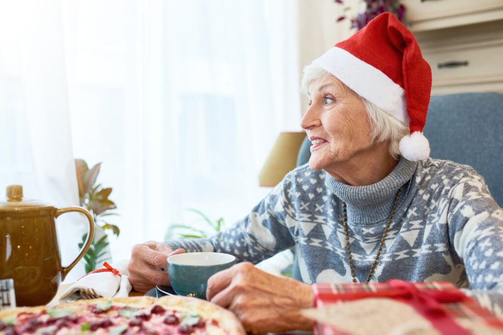 Senior woman in Santa hat at long-term care facility celebrating holidays, drinking tea and looking out the window