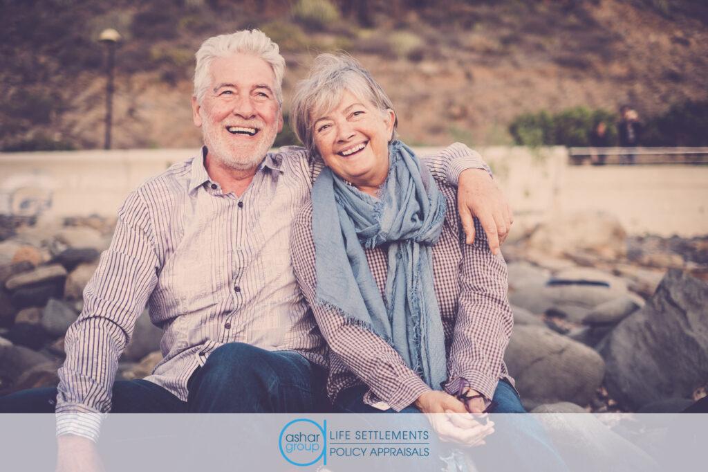 happy senior couple sitting on the beach