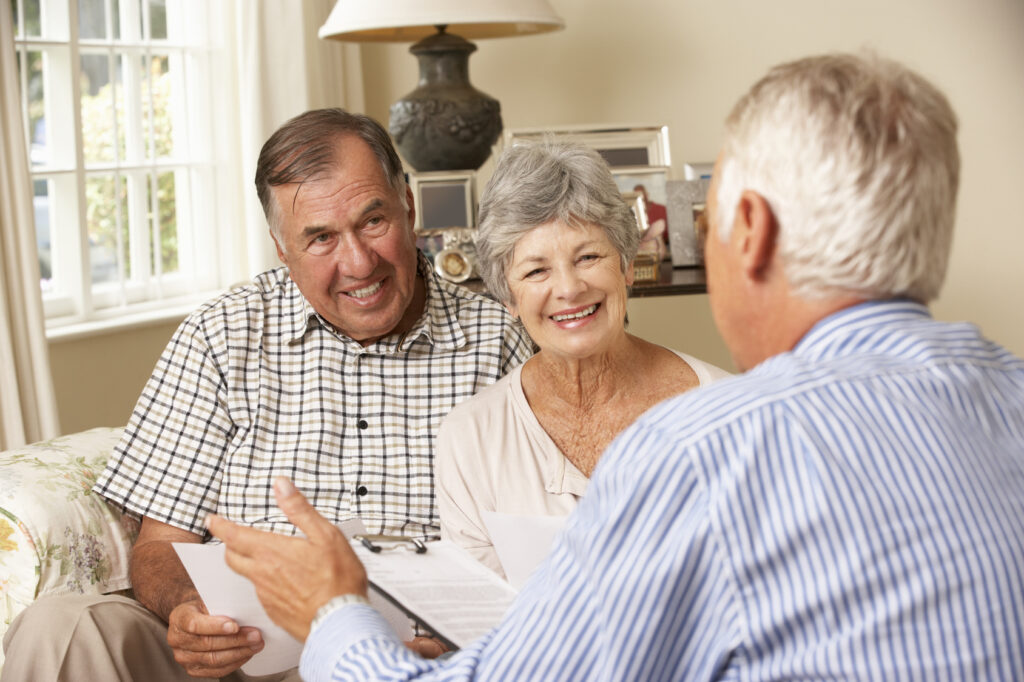 Financial advisor talking to smiling senior couple after completing a life settlement