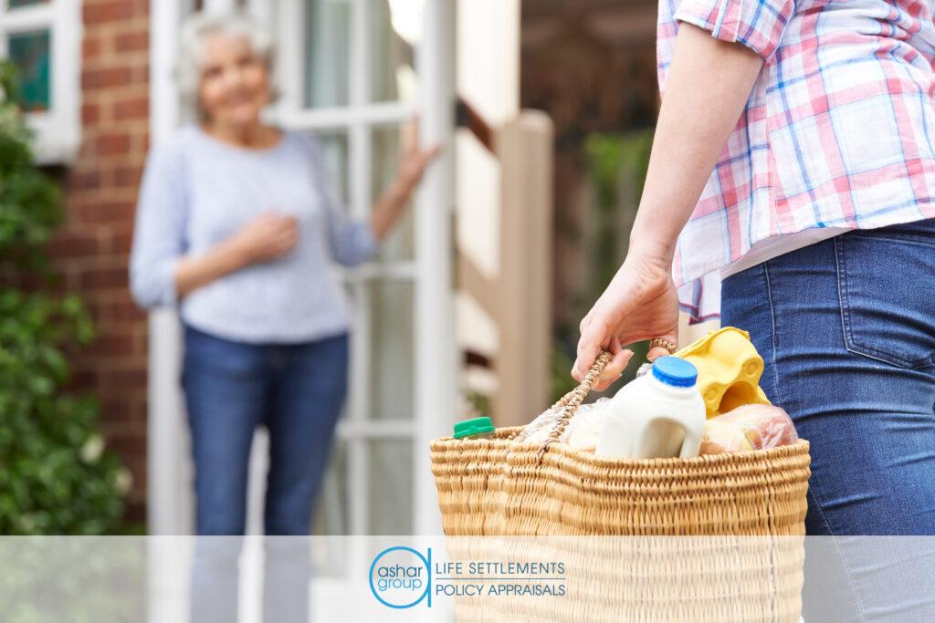 Neighbor in senior village bringing groceries to elderly woman