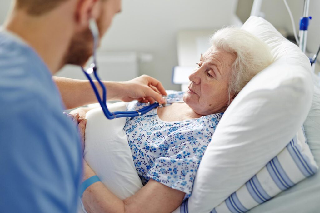 Senior woman lying in hospital bed with doctor listening to heartbeat