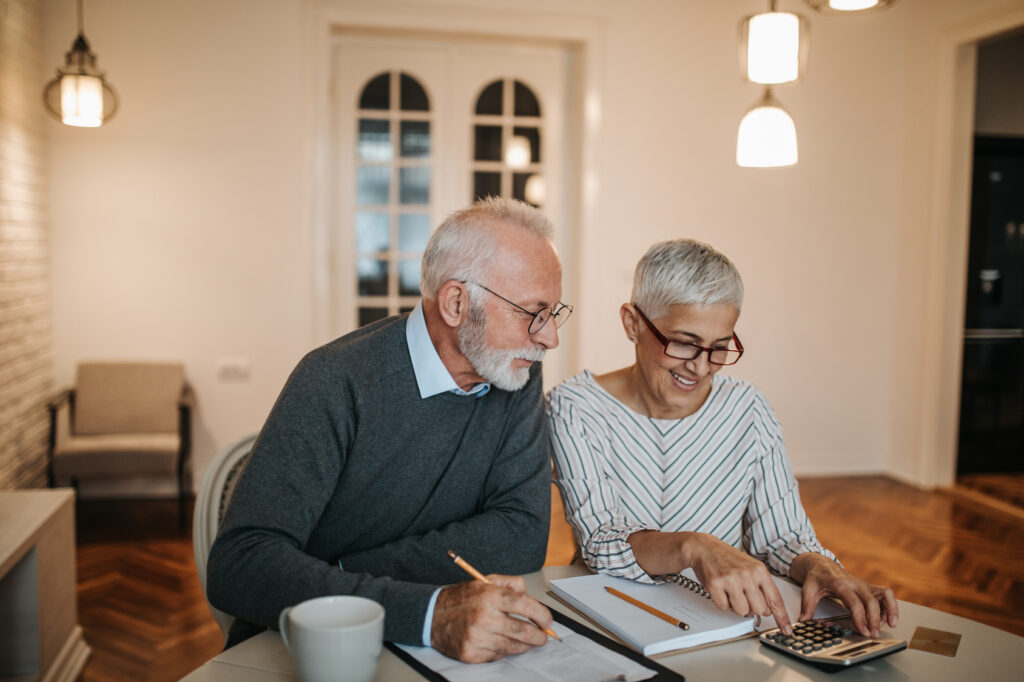 happy retired couple looking over their finances with a calculator